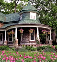 Round porch with hanging baskets ~ I am fascinated by the round room, round porch, round peak at the upper level! How charming!