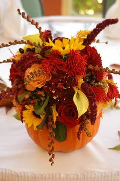 for your thanksgiving center piece cut hole in pumpkin then place mason jar in it with your bouquet and water in it.  using your seasonal colors of flowers and adding red red roses to that bouquet. it perfect.