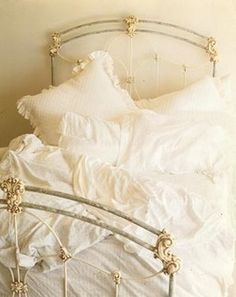 Chic wrought iron bed with clean white *ruffled* spread