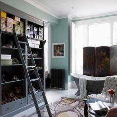 A charming bathroom/dressing room boasts soft green walls against deep grey cabinetry. A silvery-grey soaking tub sits ready for an evening soak.