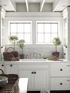 gorgeous white & gray kitchen design with crisp white glass-front kitchen cabinets, oil rubbed bronze hardware, polished nickel faucet, topiaries, baskets and marble counter tops and backsplash.