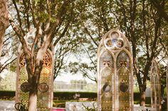 This is truly the ULTIMATE for an outdoor wedding.  What bride wouldn't love to display these incredible vintage stained glass windows? vintage wedding. outdoor wedding decor. stained glass. wedding decorations. gothic wedding.
