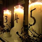dollar store candles with numbers printed on vinyl and placed on a shutter for a table center piece