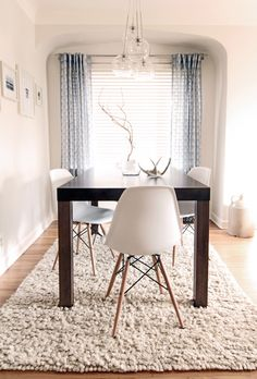 White and natural dining room with a graceful pendant light.