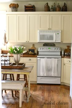 Faded Charm - love the beadboard cabinets..... Do with green stove and open shelving above with a wall of tile