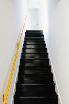 amazing accent. Black painted stairs with a yellow handrail. Via Remodelista.
