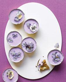 These dainty confections, iced with a pale shade of royal purple, are fit for a modern-day queen and her retinue. Dark, indulgent brownie batter is baked in gilded cupcake liners. The delicate hue of the smooth topping hints at its soothing floral flavor and aroma, which are achieved by steeping dried lavender in milk. Sugared pansies and violas form a glittering crown for the little cakes, which are rich enough to replace the pot of gold at the end of the rainbow.