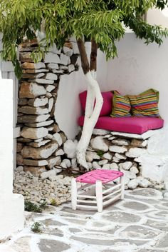 Greek style patio area. Painted tree, stonework, white, pink.