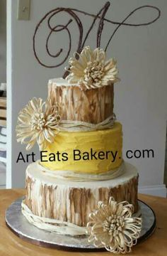 3 tier ivory, brown and yellow rustic butter cream unique modern wedding cake design with raffia flowers, ribbons and custom made monogram topper