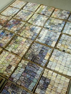 Amanda Nelsen composes pictures from thousands of pieces of junk mail, folded and string-bundled into 2 inch cubes to create colored pixels.