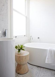Wooden block stool against an all-white bathroom