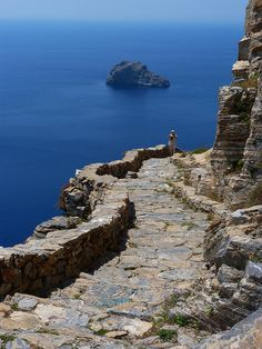 ascending the rocky stairs (about 350 steps) high above the sea toward the Monastery of Panagia Hozoviotissa, Amorgos, Greece