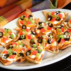 Loaded Pita Nachos | Meals.com - Chili, sour cream and melted cheddar are loaded on top of pita chips for the ultimate #gameday app! Dig in. #appetizer