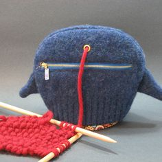 The cutest center-pull yarn ball holder made from a felted sweater sleeve. I may have to adapt my knitting bag to work like this...