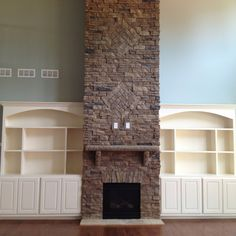Two-story stone fireplace with built-ins on either side