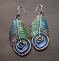 cute combination of metal charm and clay by Chris Kapono.  dangle earrings with antiqued silver metal feather charms, polymer clay and shimmery powdered pigments.