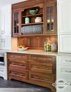 "A walnut hutch was designed to look like a ""found"" piece in this white kitchen.  It's a beautiful rust element."