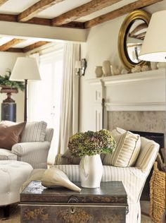 love love love the simple comfy striped slipcover chairs, the white American art pottery on the mantel and the big firewood basket. ♥