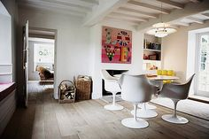 lovely mix of old and new, dining room with the modern classic Tulip table and chairs from Eero Saarinen. There is also a beautiful old fireplace with rustic baskets of firewood and lovely white-painted beamed ceiling. The creme de la creme in this room is this colourful, somewhat kitsch Love-poster.