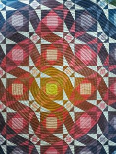Storm at Sea quilt by Beth at Central Florida Modern Quilt Guild. close up photo, free motion quilted in a spiral design that is centered over the focal point of the quilt.