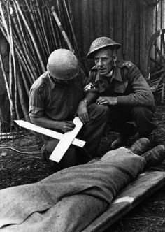 An army priest writes the name of a soldier killed in a shell burst during the fighting in France, on a makeshift cross, 1944.