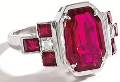 Platinum, Ruby and Diamond Ring, J.E. Caldwell.     Centered by an octagonal-shaped ruby weighing 3.96 carats, flanked by six calibré-cut rubies weighing approximately .60 carat and two French-cut diamonds weighing approximately .40 carat, size 6¼, signed JEC & Co., circa 1950. With signed box. Via Sotheby's.