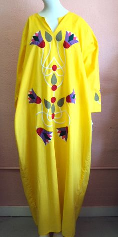 Coolness abounds in this canary colored caftan! Bright yellow cotton is appliquéd with flowers and vines on both the front and each sleeve. RetroRosiesVintage on Etsy.