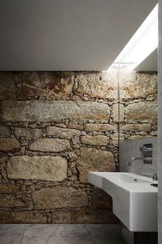 Bathroom feels underground due to the natural stone wall, and the only light source being hidden in a recess in the ceiling. It is fluorescent light but you would assume it's natural, given the atmosphere. Good solution for places/budgets where a skylight isn't possible