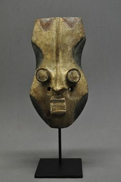 Africa | Carved wood Grebo mask with white, blue and red pigment. It has 2 tubular eyes.  Liberia.
