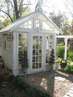 Love this greenhouse.  Look at the stained glass window at the top!
