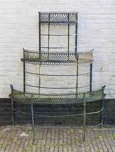 A green painted wrought-iron étagere  Late 19th century  Of demi-lune form, with three tiers with simulated wicker work baskets  162 cm. high x 134 cm. wide x 70 cm. deep