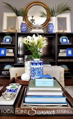 Symmetry can help bring a calm balance to a room. Using blue frames + vases from HomeGoods helps give color - even in a rental home. #Summer #LivingRoom #RentalRestyle #HappyByDesign #sponsored