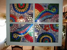 Colorful stained glass on a window with half marbles and flowers. The mosaic is grouted with dark gray.