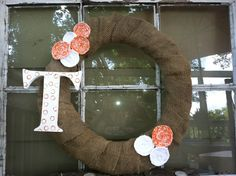 """Recycled burlap coffee bean sack wrapped around a grapevine wreath.  Hand made orange and white rosettes with a hand painted """"T"""".   Great to hang on your front door to support Tennessee football or basketball team!"""