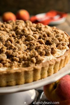 Peaches and Cream Almond Crumb Tart - Shortbread cookie crust filled with sweet cream cheese and diced peaches with a sweet almond crumb top! So delicious!