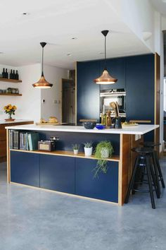 Modern kitchen featuring tall units and kitchen island with a dark blue fronts.
