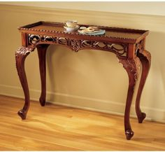 18th Century Victorian Antique Replica Hand Carved Console Table by XoticBrands. $517.12. Antique Replica Décor. Hand Carved Furnishing. Hand-carved solid mahogany replica ; With the artistic pedigree styling of 18th century England, this Victorian-influenced quality solid mahogany table is a study in balance. Graceful cabriolet legs rise to showcase delicate hand carving surrounding the fluted, ?pie-crust? tabletop. A timeless work of furniture art, each nuance will ga...