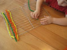 weaving pipe cleaners through a cooling rack to promote fine motor skills