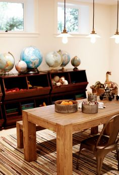 Playroom with Parsons-style table, storage boxes, industrial pendants, and collection of globes.