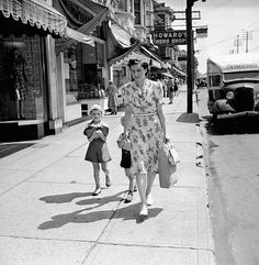 A woman (Mrs. Jack Wright) and her sons carrying groceries home on a sunny day in September 1943. mother