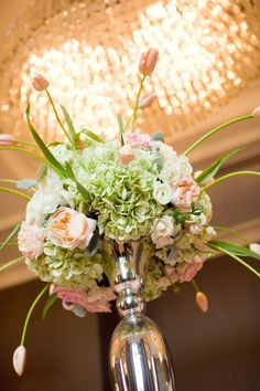 Towering centerpiece of hydrangeas, roses and tulips. Too pretty!