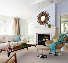 A Modern Beach House:   With clean lines, a cool palette, and vintage vacations finds, this beach house has a chic modern flair. Chic Family Room:   The three main living areas are located in the back of the house: a sunroom, family room, and sitting room. The beachy neutral theme extends into each room through soft blue walls and crisp white furniture. Highlighted over the mantel in the family room, a driftwood mirror adds an extra touch of natural character.