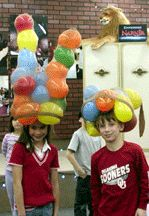 """Divide into teams of three. Have a ton of 6 -8"""" balloons blown up in advance and a new pair of ladies pantyhose for each team. Each team is to see how balloons they can stuff into the pantyhose as creatively as possible making a hat for one of their team members. The audience votes for the winning team."""