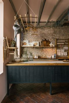 Rustic kitchen inspiration from the Sebastian Cox Kitchen by deVOL in their New York showroom. The exposed brick wall and rich terracotta floor tiles give this small room so much authenticity. #deVOLKitchens #KitchenDesignIdeas #RusticKitchen #ModernCountryKitchen