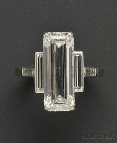 Important Platinum and Diamond Ring, Cartier, set with an emerald-cut diamond measuring approx. 18.90 x 7.20 x 5.30 mm, and weighing approx. 7.75 cts., flanked by baguette-cut diamonds   $88,875
