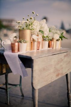wedding centerpieces...love that you can use found containers and spray paint for an inexpensive centerpiece!  If you used the plank table runners these would look nice on that.