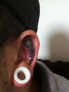inside the ear peacock feather tattoo