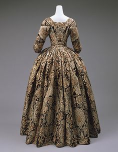A Spitalfields silk dress with a dome-shaped skirt conforms not only to the silhouette of the 1730s but also to the interaction between silks and laces during that time, especially evident in Spitalfields manufacture. The silk pattern is like that of lace. While most eighteenth-century dresses have been altered in some way for subsequent use, fashion historian Janet Arnold has noted that this one shows no sign of ever having been altered and is thus in its perfect original state.
