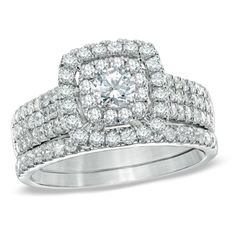 A double cushion-shaped frame, set with shimmering round accent diamonds, wraps this center stone in a sparkling embrace.