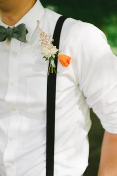 orange boutonniere + suspenders, photo by Michelle Gardella http://ruffledblog.com/glittery-webb-barn-wedding #grooms
